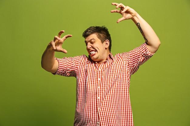 叫び、憎しみ、怒り。緑のスタジオの背景で叫んで泣いている感情的な怒っている男。感情的な、若い顔。男性の半身像。人間の感情、表情の概念。トレンディな色 無料写真