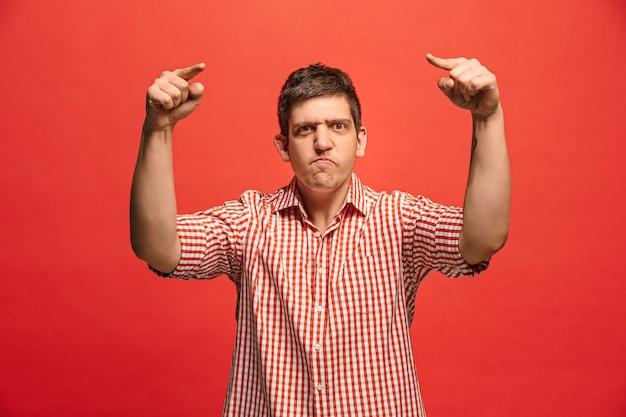 叫び、憎しみ、怒り。赤いスタジオの背景で叫んで泣いている感情的な怒っている男。感情的な、若い顔。男性の半身像。人間の感情、表情の概念。トレンディな色 無料写真