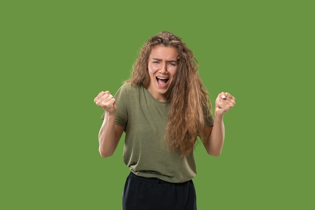 Screaming, hate, rage. crying emotional angry woman screaming on green studio background. emotional, young face. Free Photo