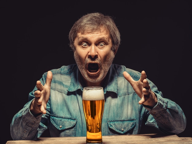 Screaming man in denim shirt with glass of beer Free Photo