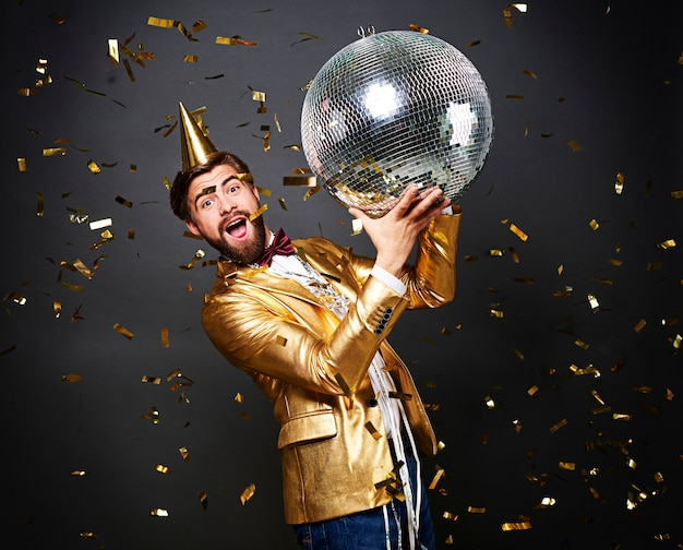 Screaming man with birthday hat holding disco ball Free Photo