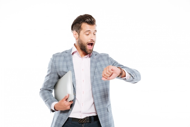 Screaming young man holding laptop computer looking at watch. Free Photo