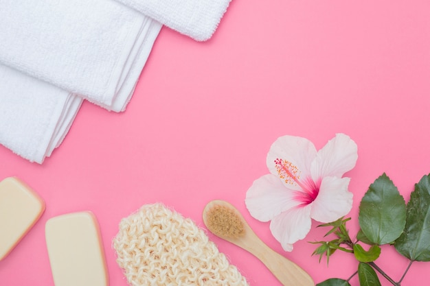 Scrub glove; brush; hibiscus flower; soap and towel on pink background Free Photo