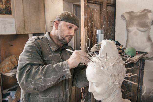 Скульптор человек работает в своей мастерской Premium Фотографии