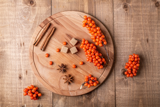 Sea-buckthorn berries and spice on wooden background. rustic style. Premium Photo