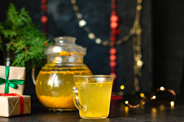 Облепиховый чай в чайнике и в прозрачной чашке на столе рождественское чаепитие новогодний гостеприимный напиток Premium Фотографии