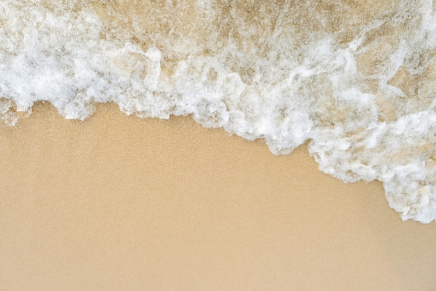 The sea keep kissing the shoreline, top view white wave on sand with copy space. Premium Photo