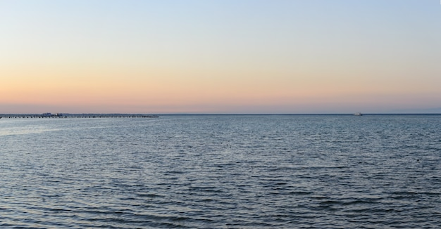 Sea shore yacht on the horizon and pier in the evening panorama Premium Photo
