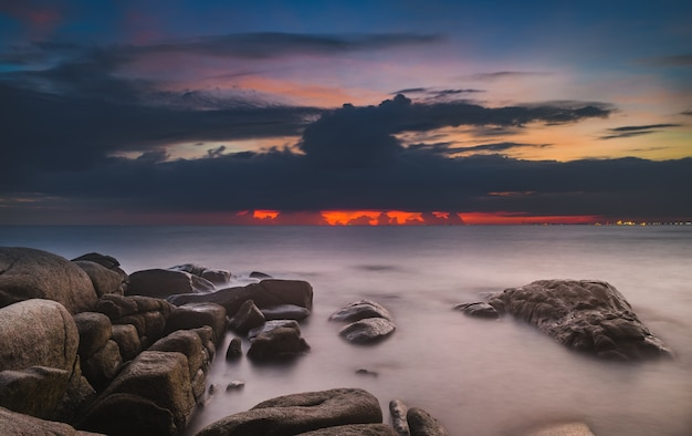 Sea stones and cloud sky in sunset time lighting and dark shadow. Premium Photo