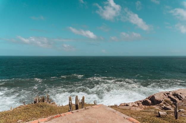 Море в окружении холмов, покрытых кактусами и скалами, под голубым небом и солнечным светом Бесплатные Фотографии