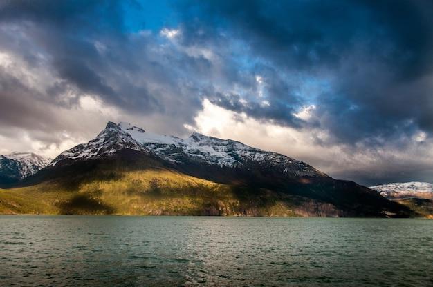 Mare circondato da montagne sotto un cielo nuvoloso in patagonia, cile Foto Gratuite