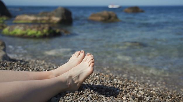 日焼けした女性の足を洗う海の波。夏休みの海岸でリラックスした美しい若い女性。晴れた日にビーチに横たわっている女の子の足。スローモーションを閉じる Premium写真