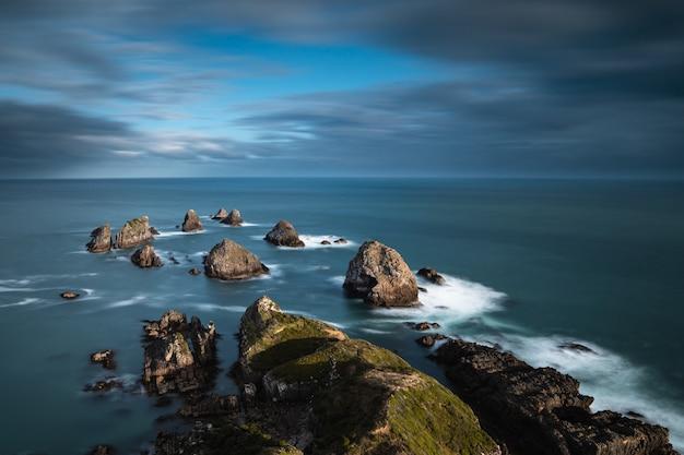 青い曇り空の下で水に大きな岩のある海 無料写真