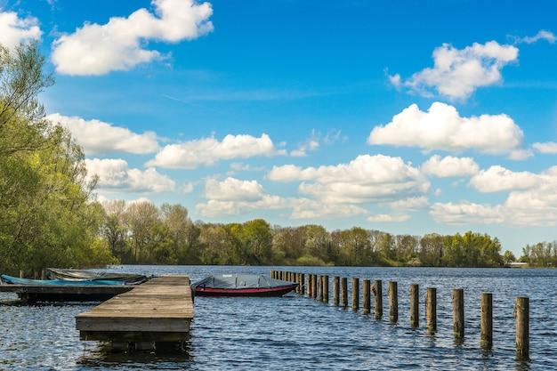 Mare con barche vicino al molo e verdi alberi in lontananza sotto un cielo blu Foto Gratuite