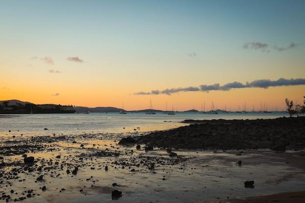 Mare con navi su di esso circondato dalla spiaggia e dalle colline durante il tramonto la sera Foto Gratuite