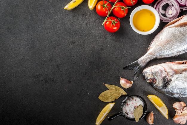 新鮮な生の有機魚ドラドseaレモントマトを調理するための材料とタマネギ塩コショウベイリーフグリーンオイル Premium写真