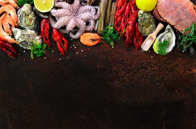 Seafood background - fresh mussels, molluscs, oysters, octopus, razor shells, shrimps, crab, crawfish, crayfish, seaweed, lemon, spices. Premium Photo