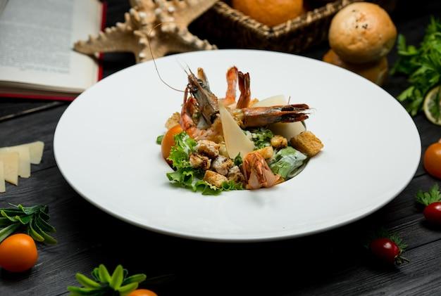 Салат из крабов из морепродуктов со свежим пармезаном, крекерами, зеленью внутри белой тарелки Бесплатные Фотографии