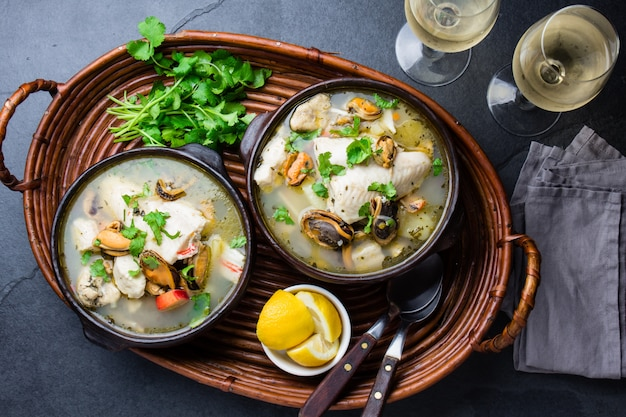 Seafood fish soup in clay bowls served with cold white wine. Premium Photo