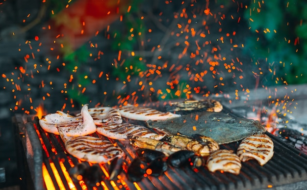 Seafood on the grill, mussels, shrimp, squid and fish are cooked on fire. Premium Photo