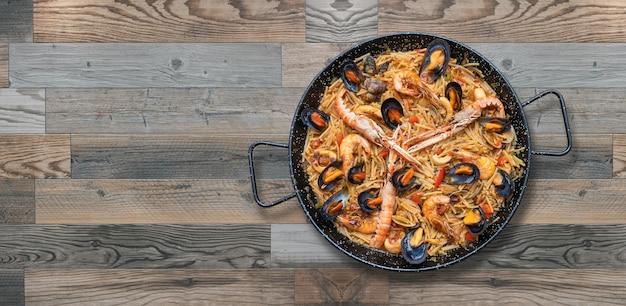 シーフードパスタパエリア、木製の背景に分離されたスペイン料理、コピースペース Premium写真