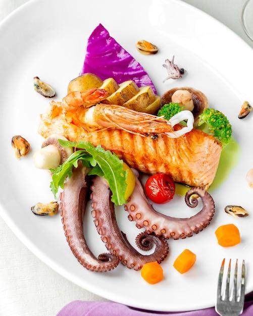 Морепродукты с жареным на гриле лососем осьминогом, мидиями, креветками, грибами и картофелем Бесплатные Фотографии
