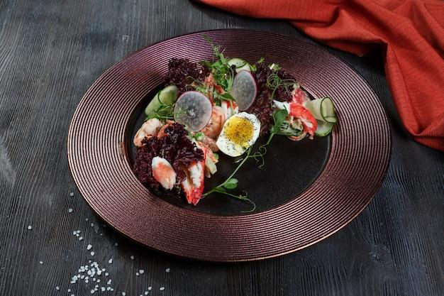シーフードサラダエビ、ムール貝、イカ、玉ねぎ、ネギをレモンとパセリで飾ったサラダ。 Premium写真