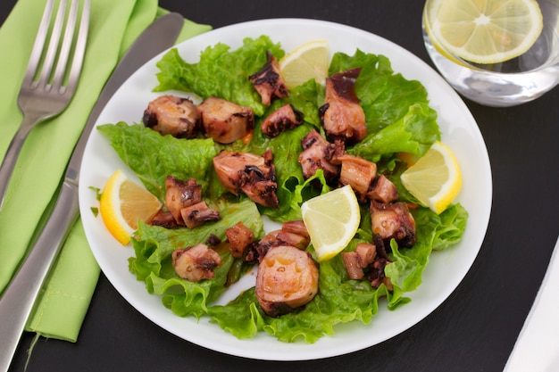 Seafood salad with lemon on the plate and glass of water Premium Photo