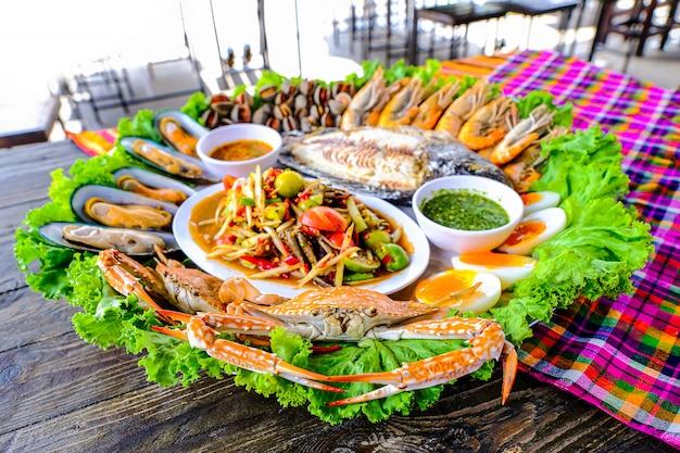 Seafood somtum has clams, shrimp, crabs, boiled eggs, grilled tilapia Premium Photo