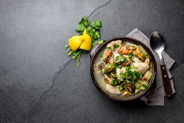 Seafood soup in clay bowl on gray slate Premium Photo