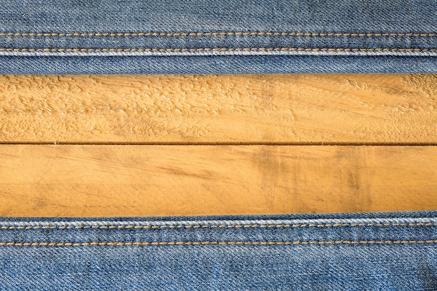 Seam of blue jeans on wooden texture Free Photo