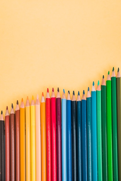 Seamless colorful pencils arranged in row on yellow surface Free Photo