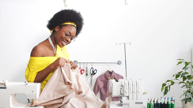 Seamstress Dressmaker African American Woman Smiles At The Camera In The Tailoring Studio African American Woman Works In Her Workshop On Self Isolation Premium Photo