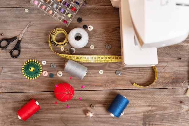 Seamstress or tailor background top view with sewing tools, colorful threads, sewing machine. Premium Photo