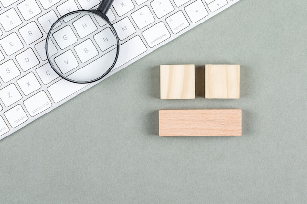 Search concept with magnifier, wooden blocks, keyboard on gray background top view. horizontal image Free Photo