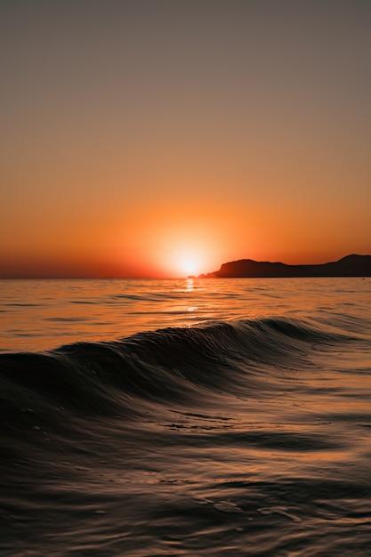 澄んだ空と夕日の波と海の風景 無料写真