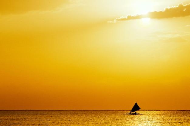 Морской пейзаж с золотым закатом и парусной лодкой посреди океана Бесплатные Фотографии