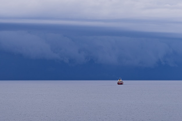 Seascape with large thunderstorm clouds above sea surface with tugboat Premium Photo