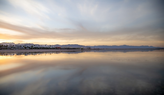 Seascape with a reflecting sky. the sun sets over the city near the mountains. Free Photo