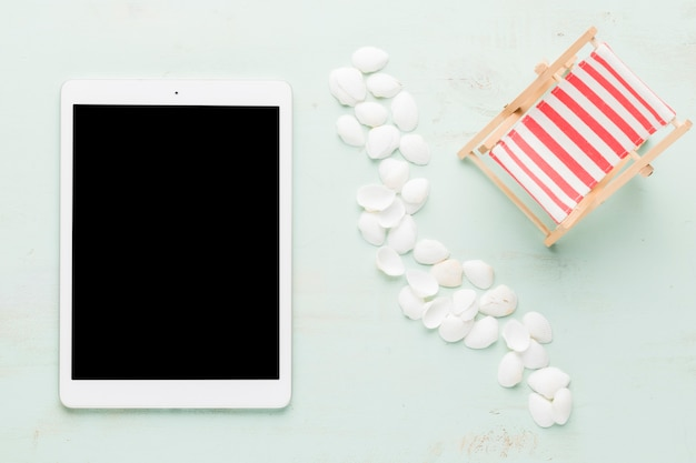 Seashells and tablet on light surface Free Photo