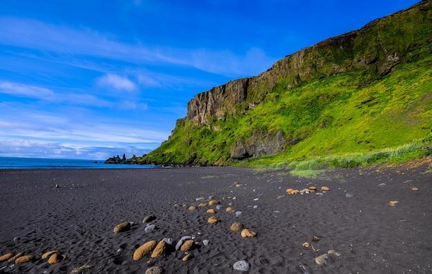 Берег моря возле травянистого холма и скалы на фоне голубого неба Бесплатные Фотографии