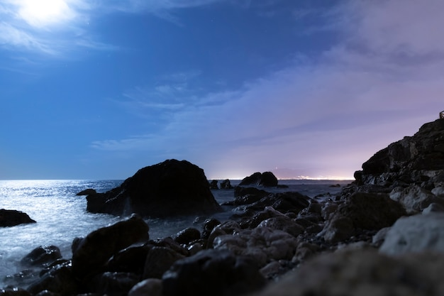 Seaside landscape in the night with rocks Free Photo