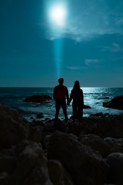 Seaside night walk and couple holding hands Free Photo
