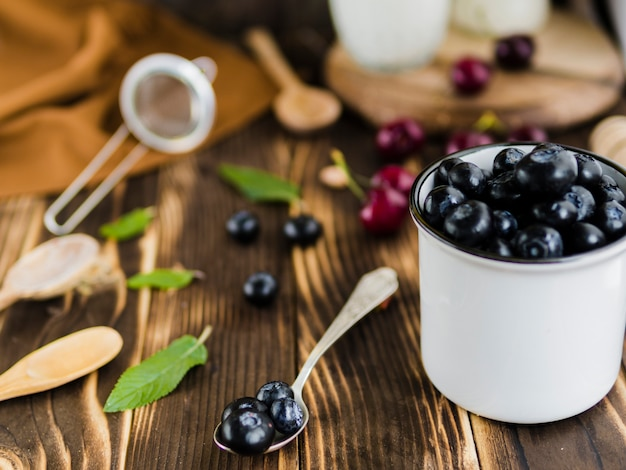 Seasonal blueberry berries in mug on table Free Photo