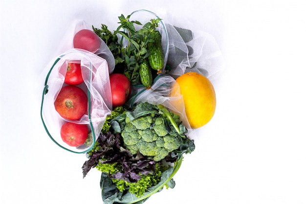 Seasonal fruits and vegetables on white. raw organic fresh food from market. zero waste shopping. reusable grocery bags Premium Photo