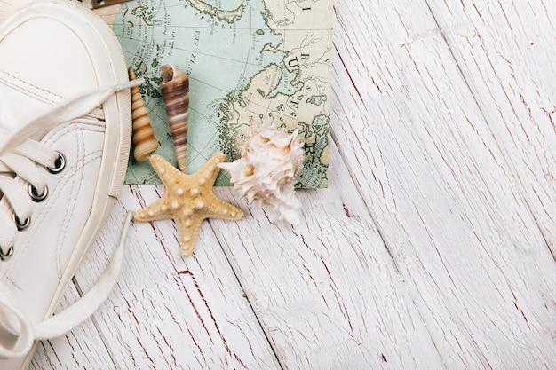 Seastars lie behind white keds on travel map Free Photo
