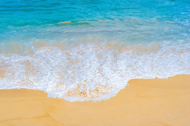 Seawater waves splash on sandy beach Premium Photo