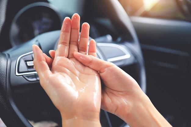 ハンドルの車内の細菌やウイルスを破壊するための手指清掃。 secapeコロナウイルスの概念からの生活 Premium写真