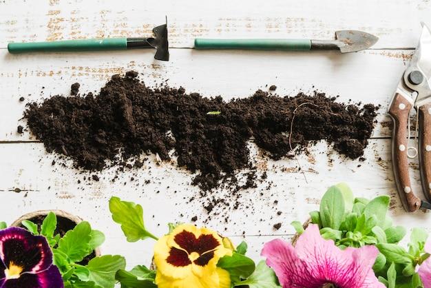 土と園芸植木鉢の俯瞰。 secateursと木製の机の上の園芸工具 無料写真