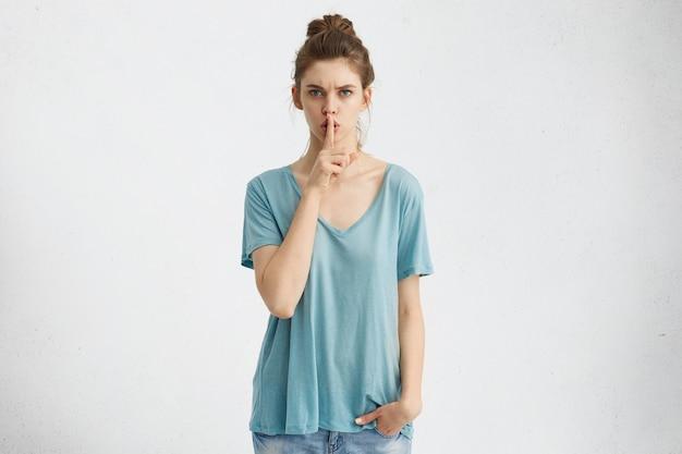 秘密性、プライバシー、機密性。人差し指を唇に当てて深刻な厳格な表情を持つ魅力的な若い女性 無料写真